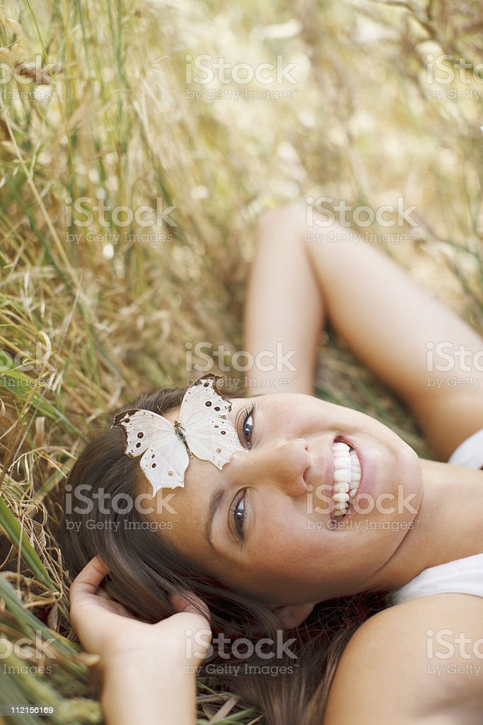 Woman laying in grass with butterfly on her forehead royalty-free stock photo