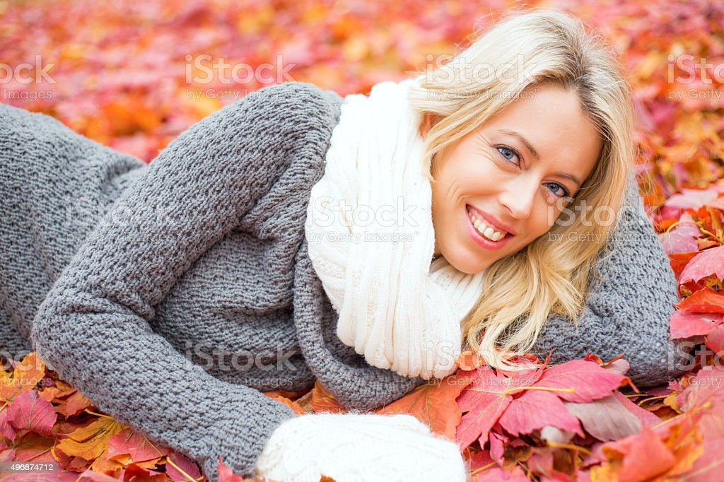 Woman laying in red leafs and smiling stock photo
