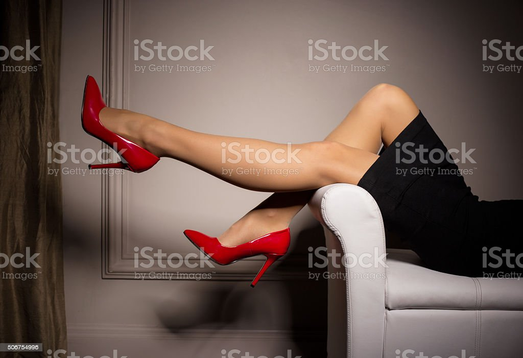 Woman laying in sofa with red high heels on stock photo