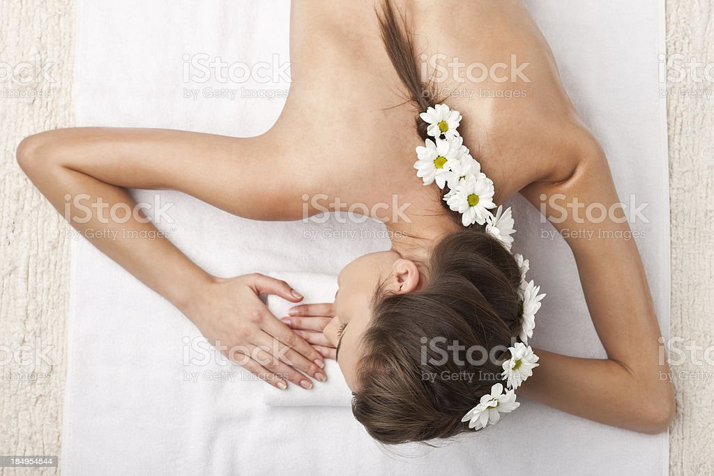 woman laying on a white towel at the spa royalty-free stock photo