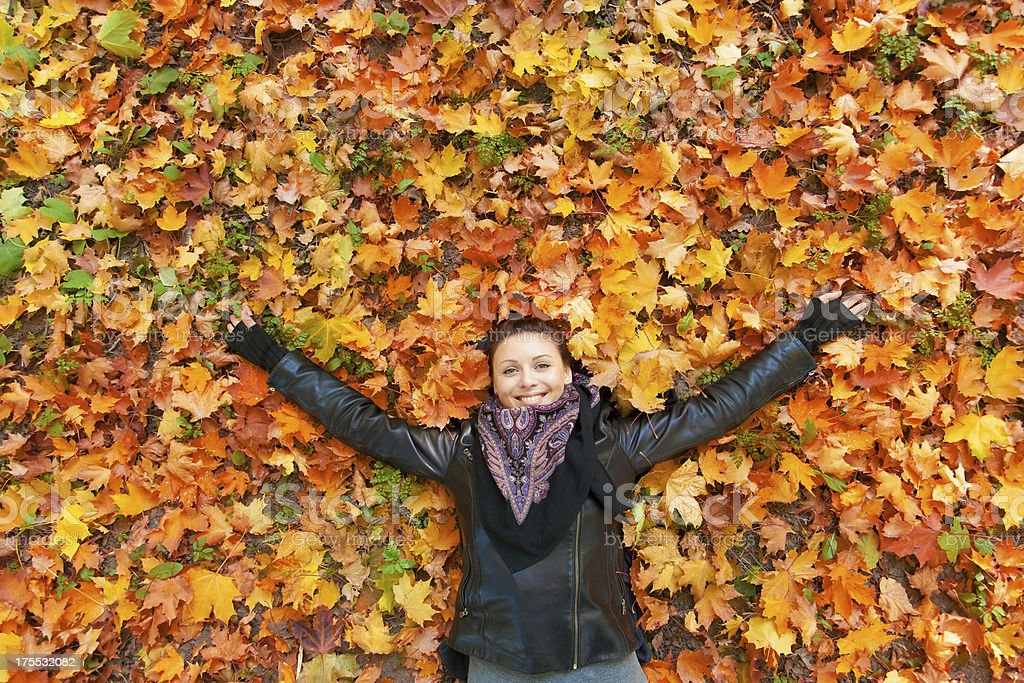 Woman  laying on autumn leaves. stock photo