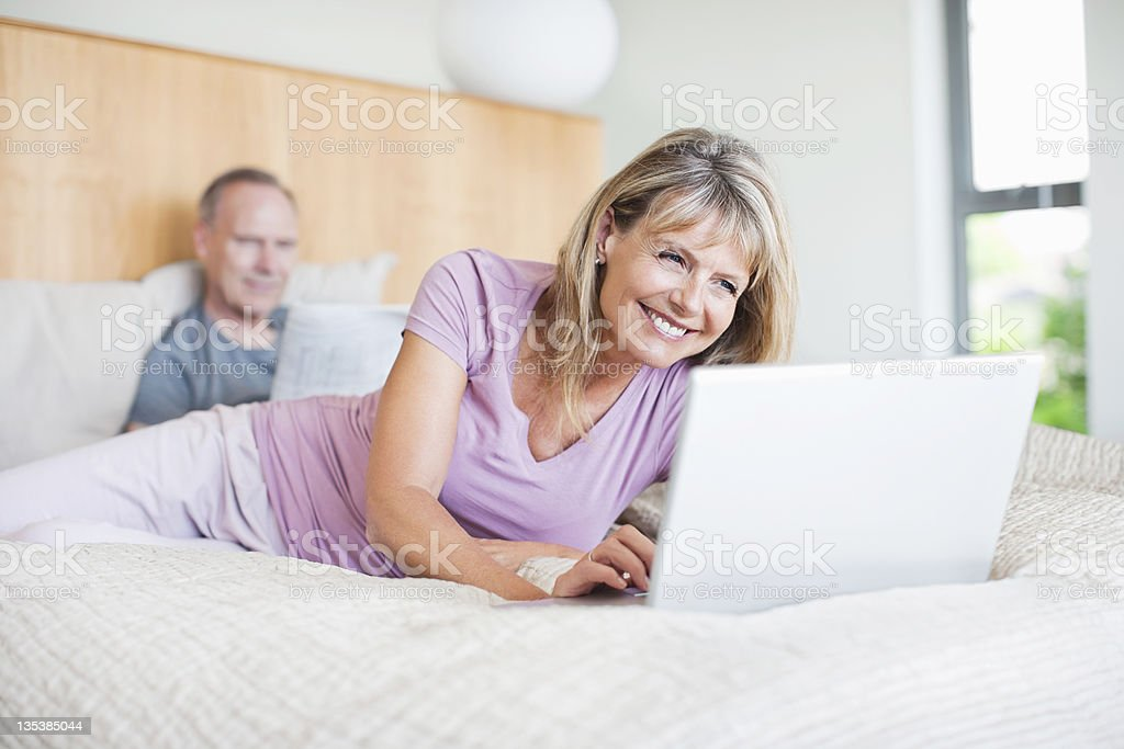 Woman laying on bed using laptop royalty-free stock photo