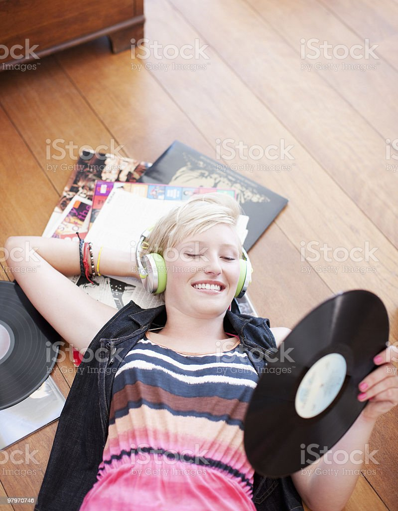 Woman laying on floor listening to headphones and holding music record royalty-free stock photo