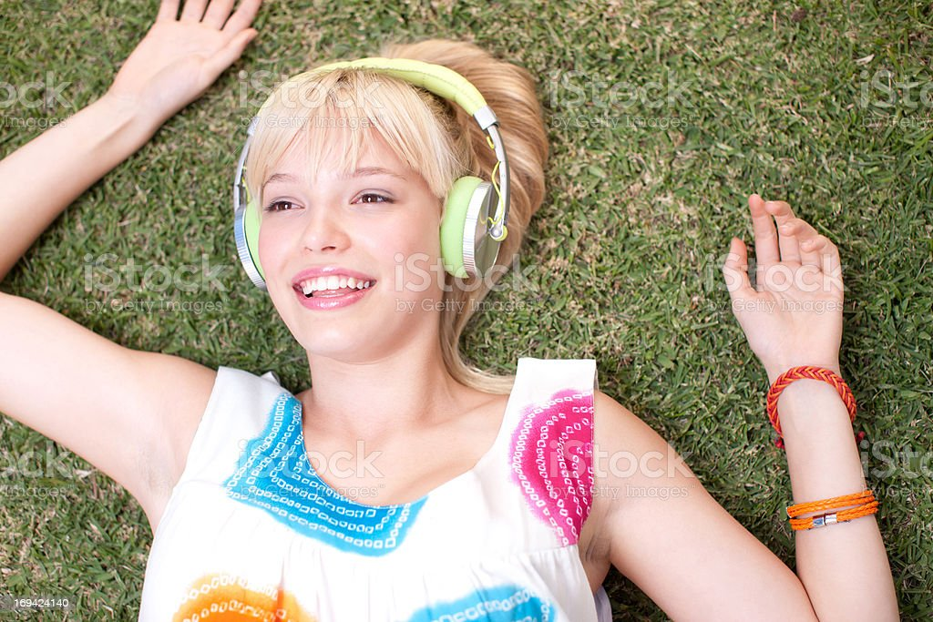 Woman laying on grass listening to headphones stock photo