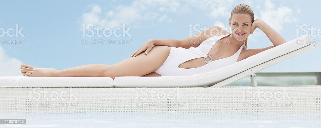 Woman laying on lounge chair at poolside stock photo
