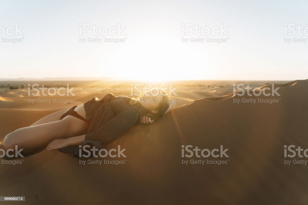 Woman laying on sand in the desert stock photo