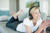 Woman laying on sofa listening to headphones
