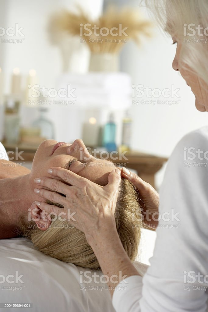 Woman laying on table having her head massaged royalty-free stock photo
