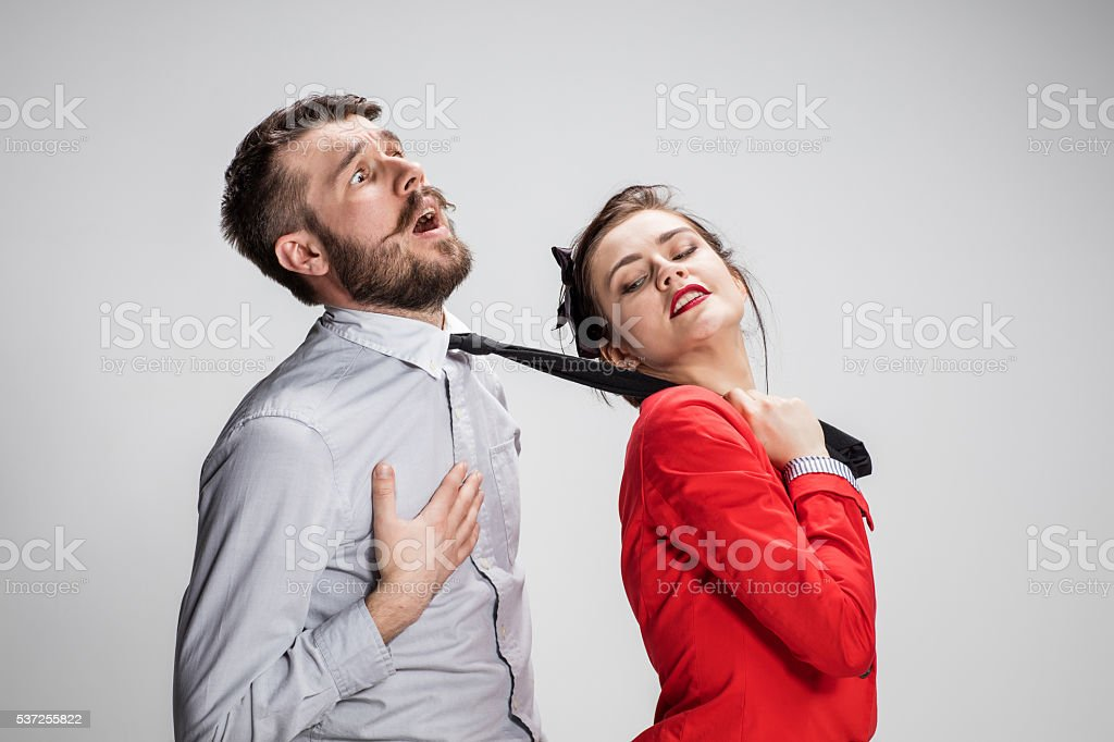 Woman leading a man by his tie stock photo