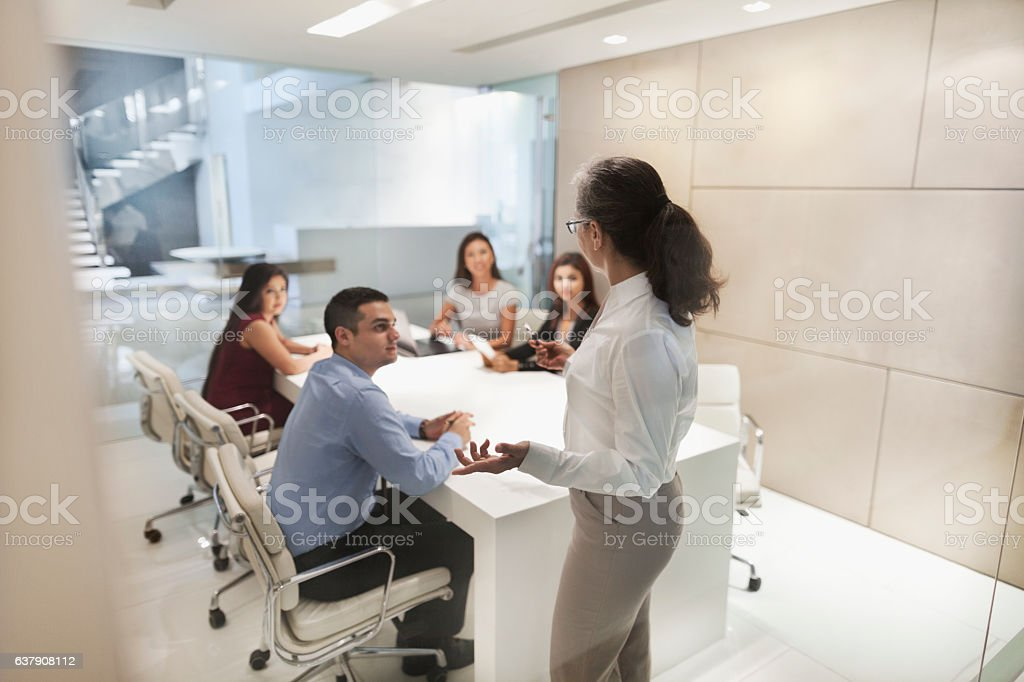 Woman leading business presentation in conference room stock photo
