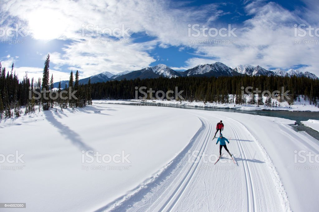 A woman leads a man on a cross-country skate ski in British Columbia, Canada. stock photo