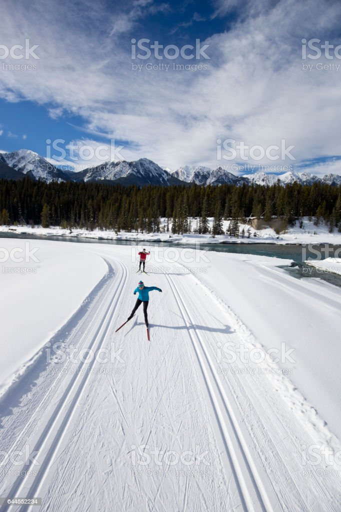 A woman leads a man on a cross-country skate ski in the Rocky Mountains of British Columbia, Canada. stock photo
