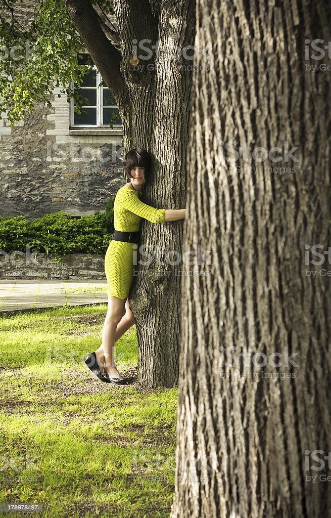 Woman lean on a thick tree royalty-free stock photo