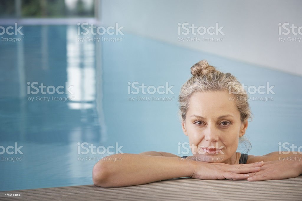 Woman leaning against an indoor pool ledge relaxed stock photo