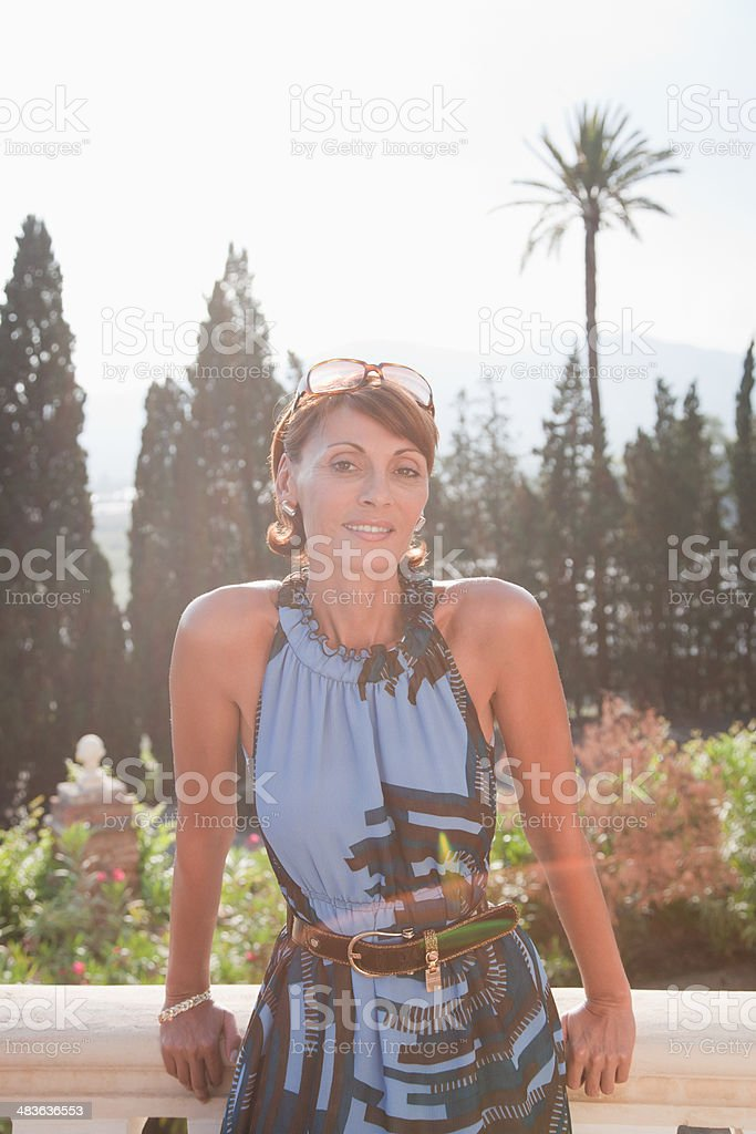 Woman leaning against balcony railing stock photo