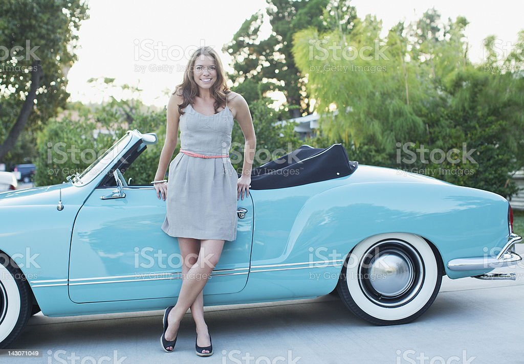Woman leaning against convertible stock photo