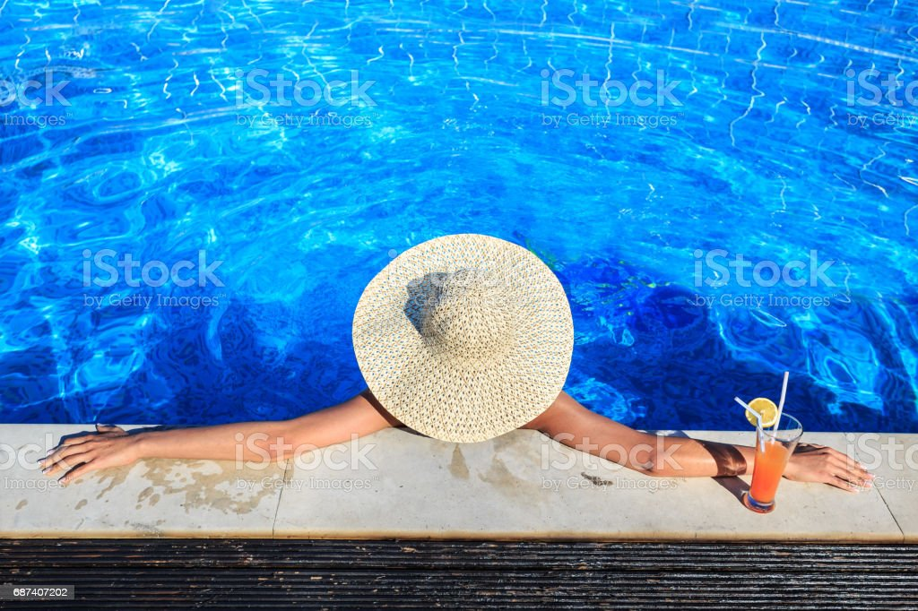 Woman leaning back on poolside stock photo