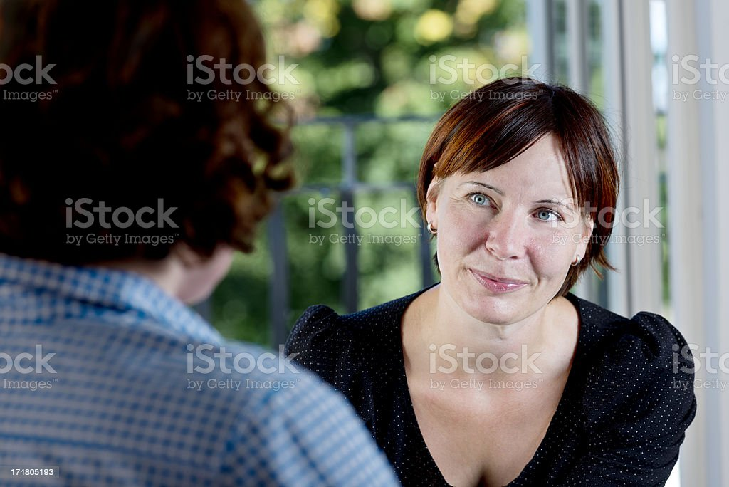 Woman leaning in and listening to a client royalty-free stock photo