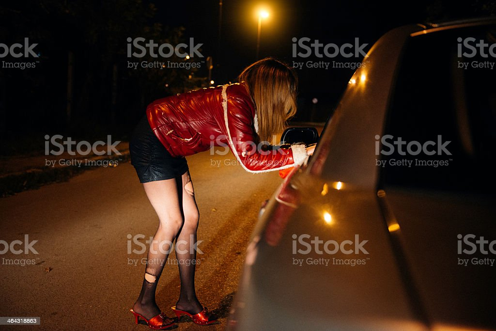 Woman leaning into car on the street stock photo