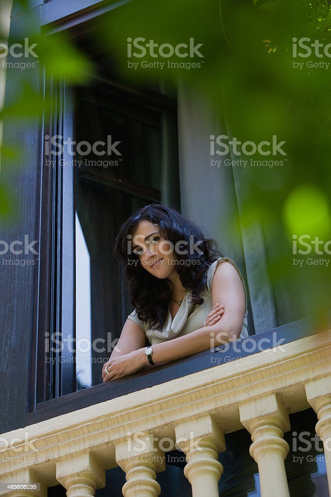 Woman leaning on balcony stock photo