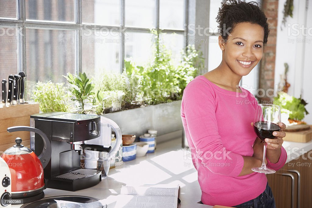Woman leaning on counter in kitchen with a glass of wine stock photo