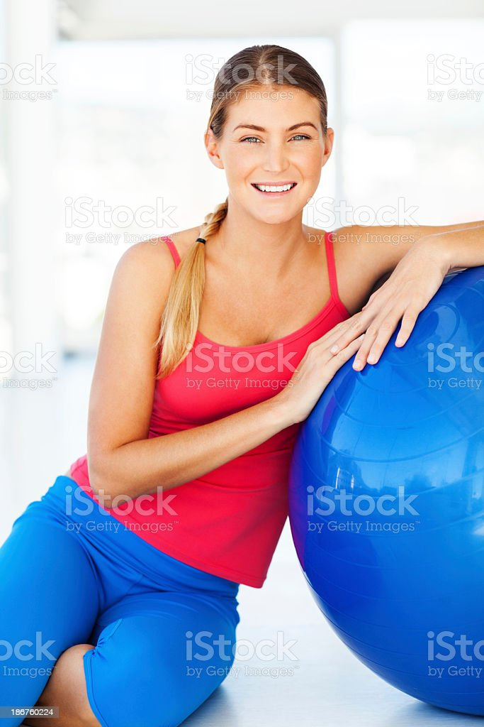 Woman Leaning On Fitness Ball While Sitting In Gym royalty-free stock photo