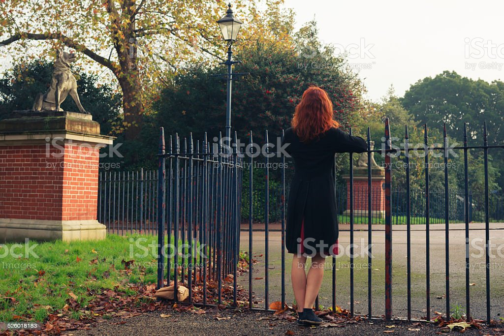 Woman leaning on gate in park stock photo