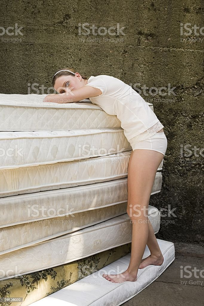 Woman leaning on mattresses stock photo