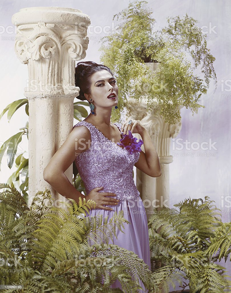 Woman leaning on pedestal and pot plants, portrait royalty-free stock photo