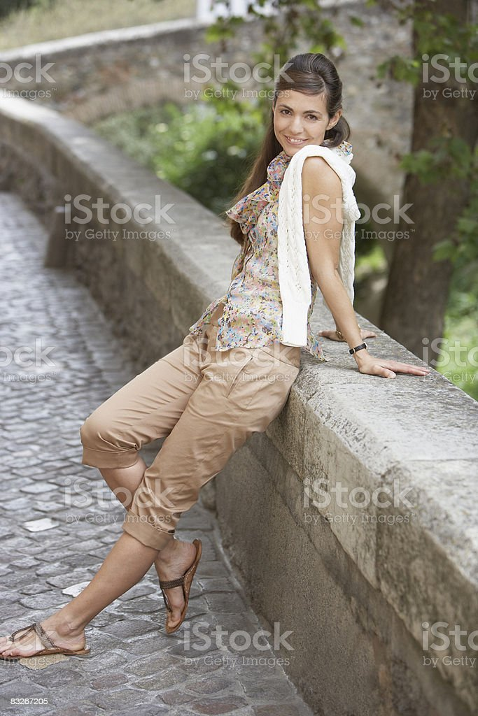 Woman leaning on stone wall royalty-free stock photo