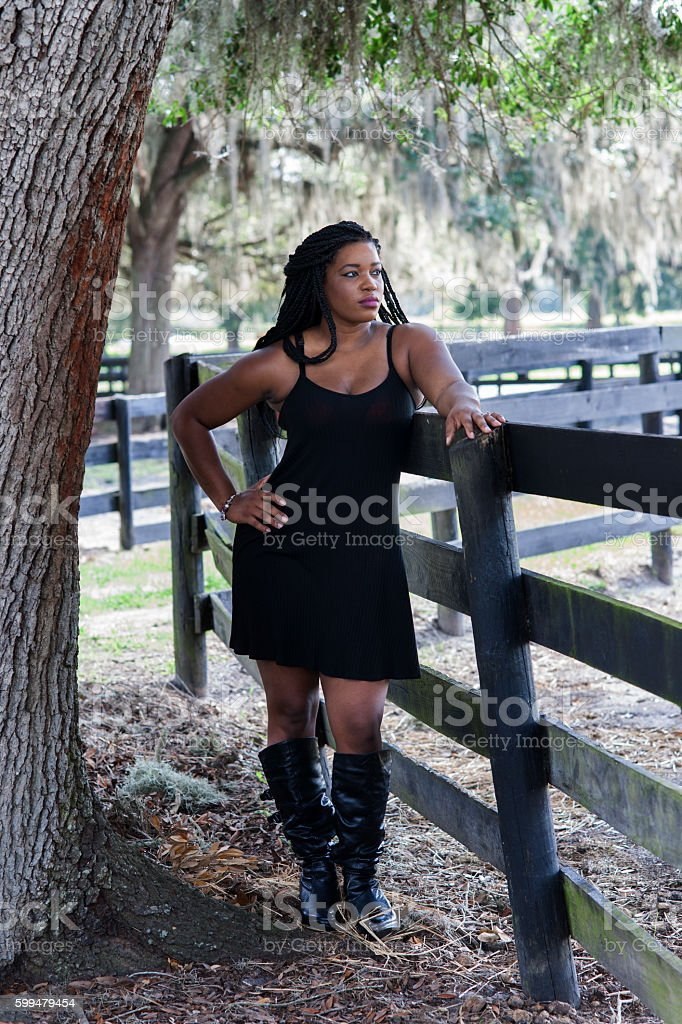 Woman leans on fence stock photo