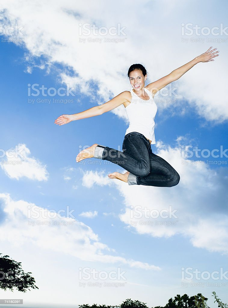 Woman leaping with blue sky and clouds stock photo