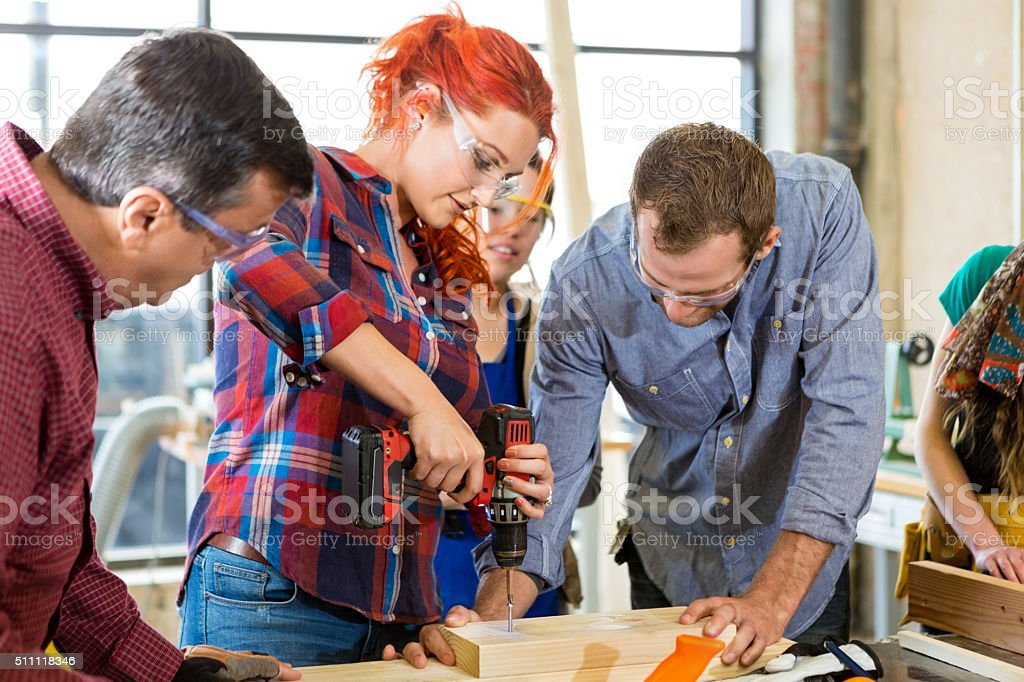 Woman learns to drill in woodworking workshop stock photo