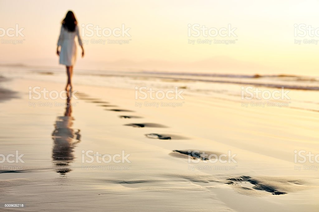 Woman leaving footprints while walking on wet sand at sunset stock photo