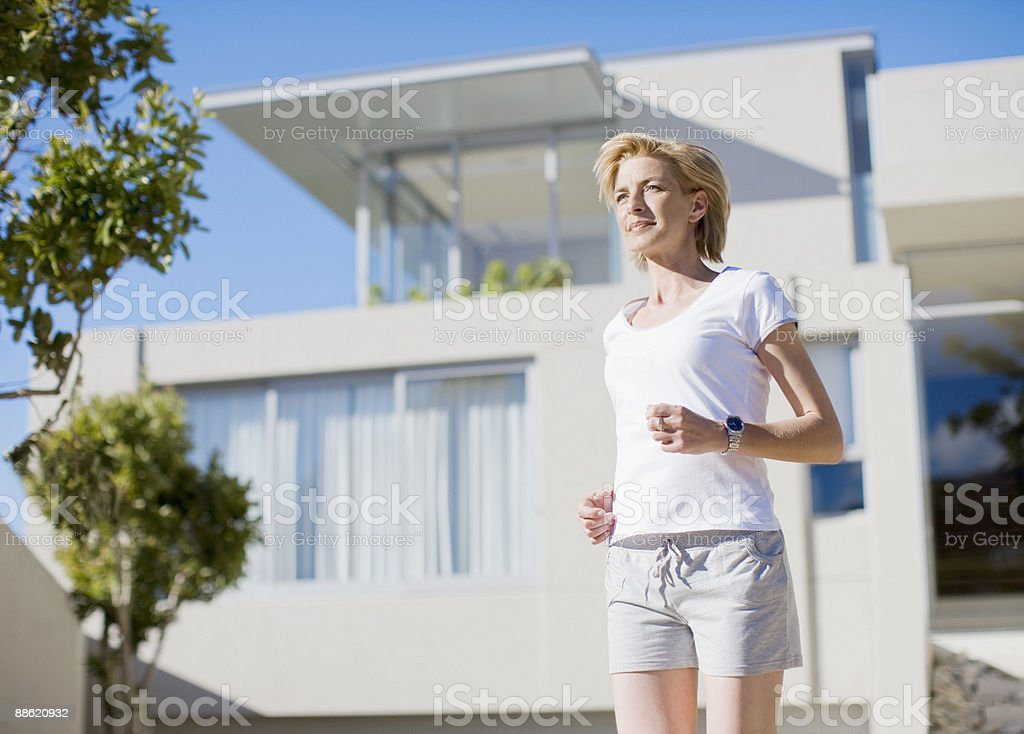 Woman leaving house to jog royalty-free stock photo