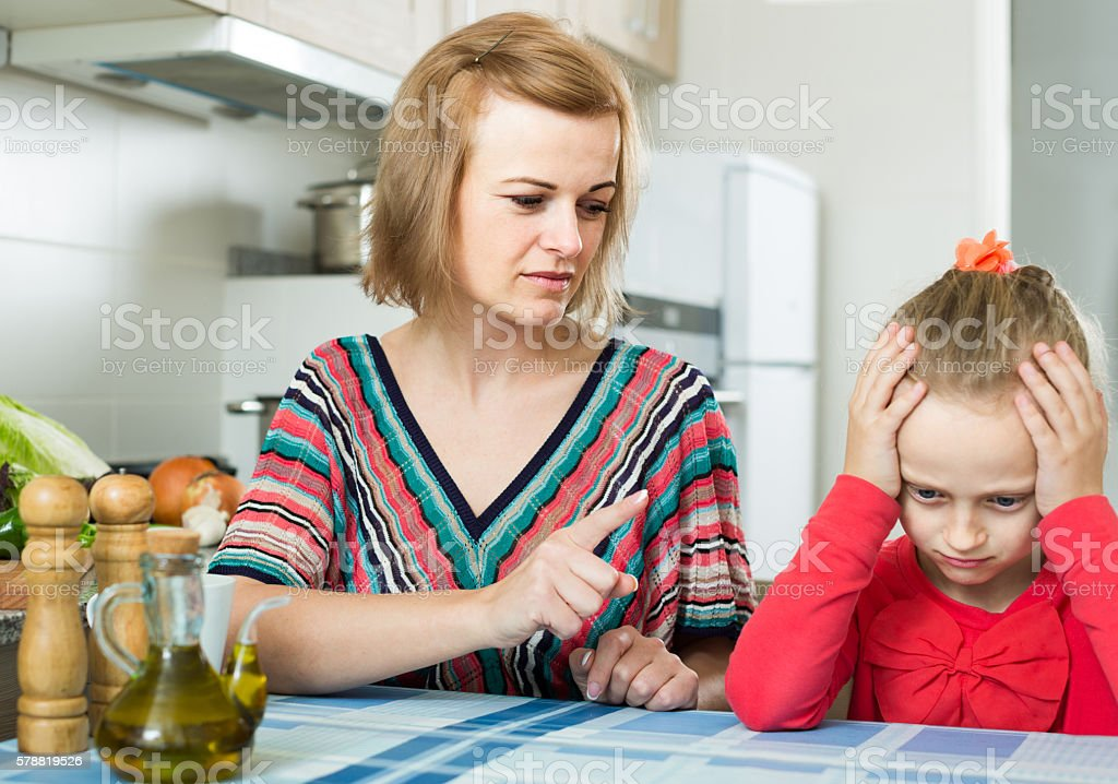 woman lecturing small female child in the kitchen stock photo