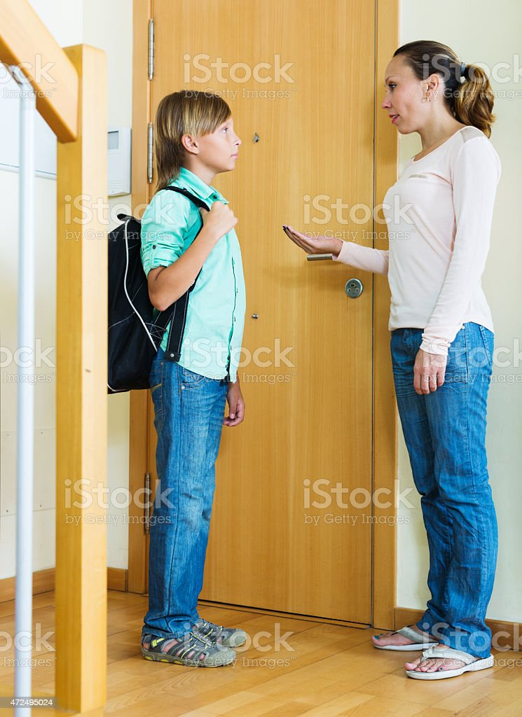 woman lecturing teenager boy before he goes to school stock photo
