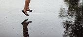 Woman legs and rain drops on asphalt