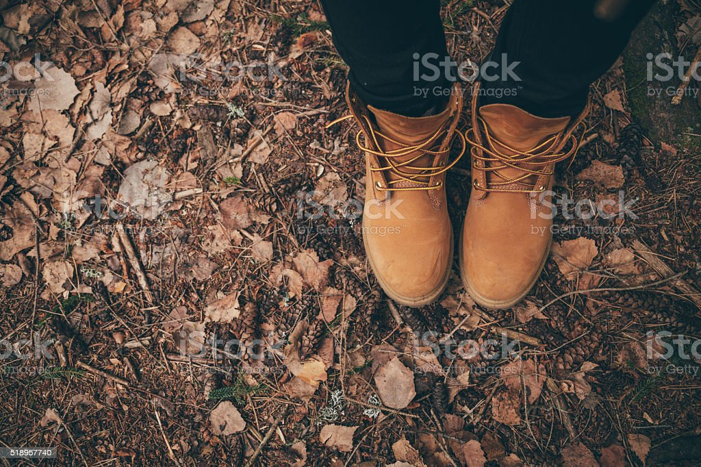 Woman legs in beige leather boots, outdoors travel concept stock photo