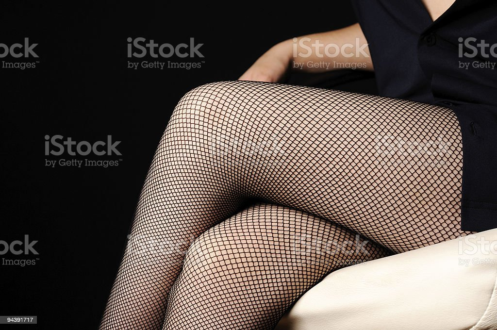 Woman legs in fishnet stockings stock photo