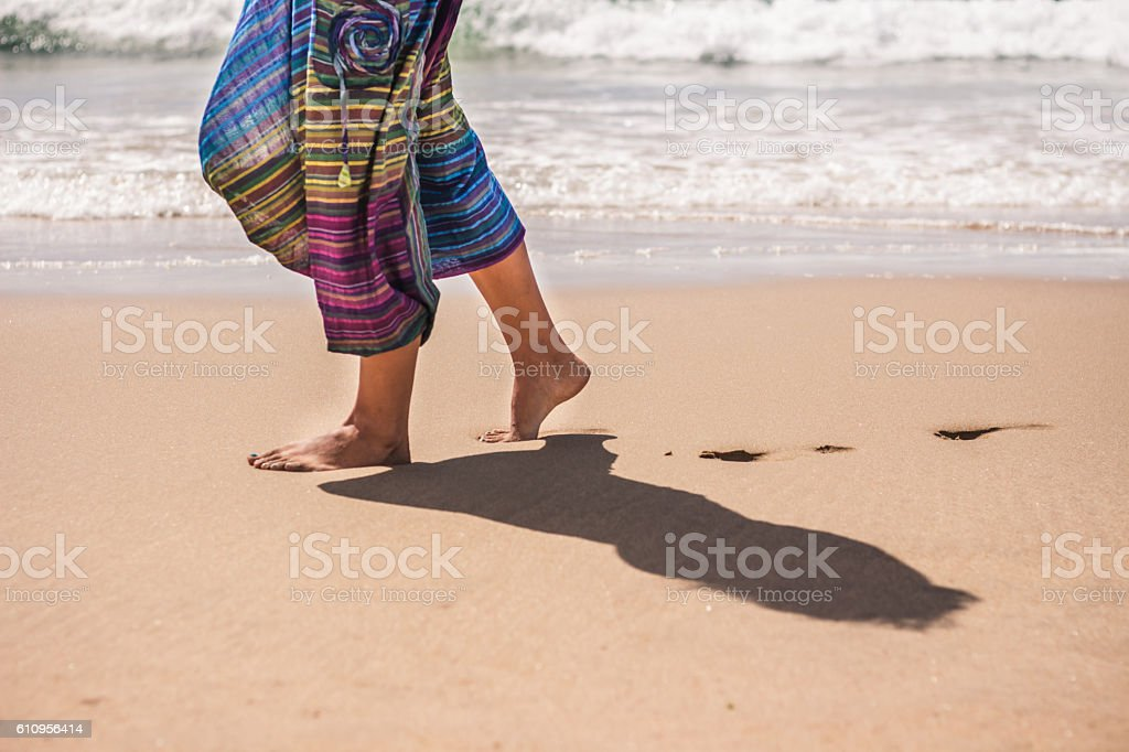 Woman legs in golden sand on beach near ocean. stock photo