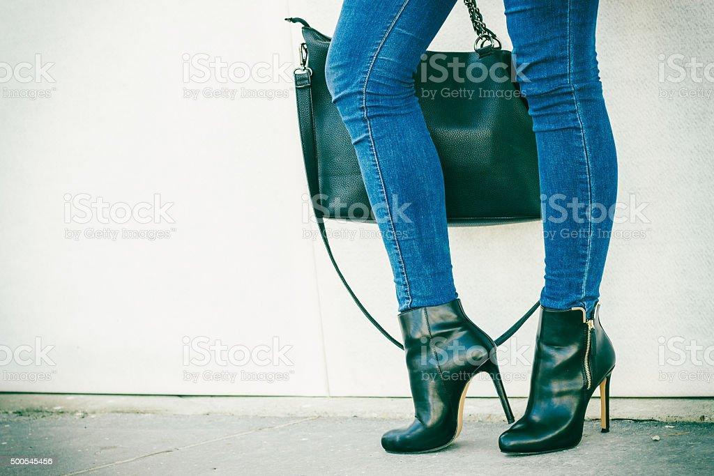 woman legs in heels shoes handbag in hand stock photo