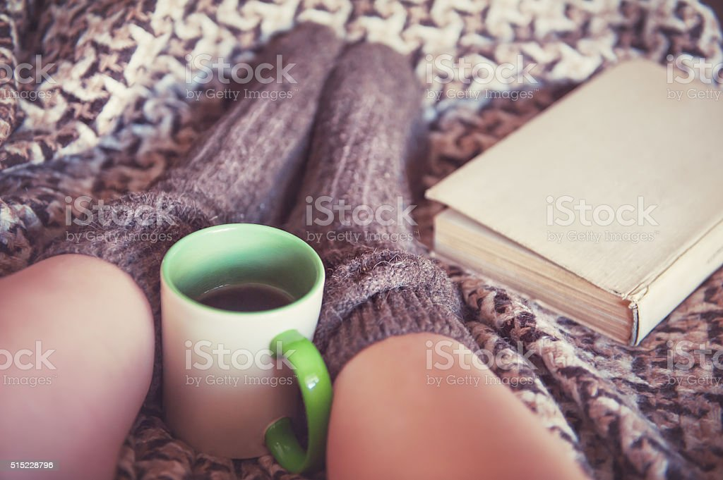 Woman legs in woolen socks with cup of tea stock photo