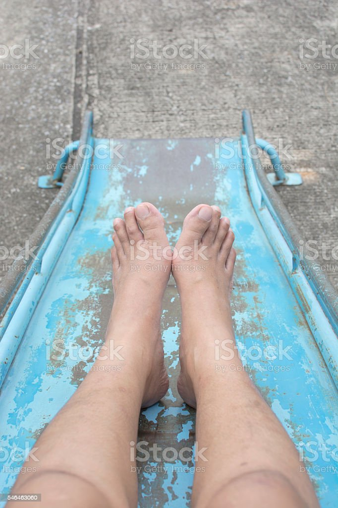 Woman Legs line on  steel slide on the playground royalty-free stock photo