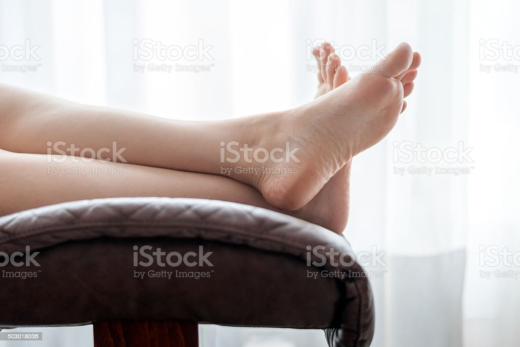 Woman legs on the chair stock photo
