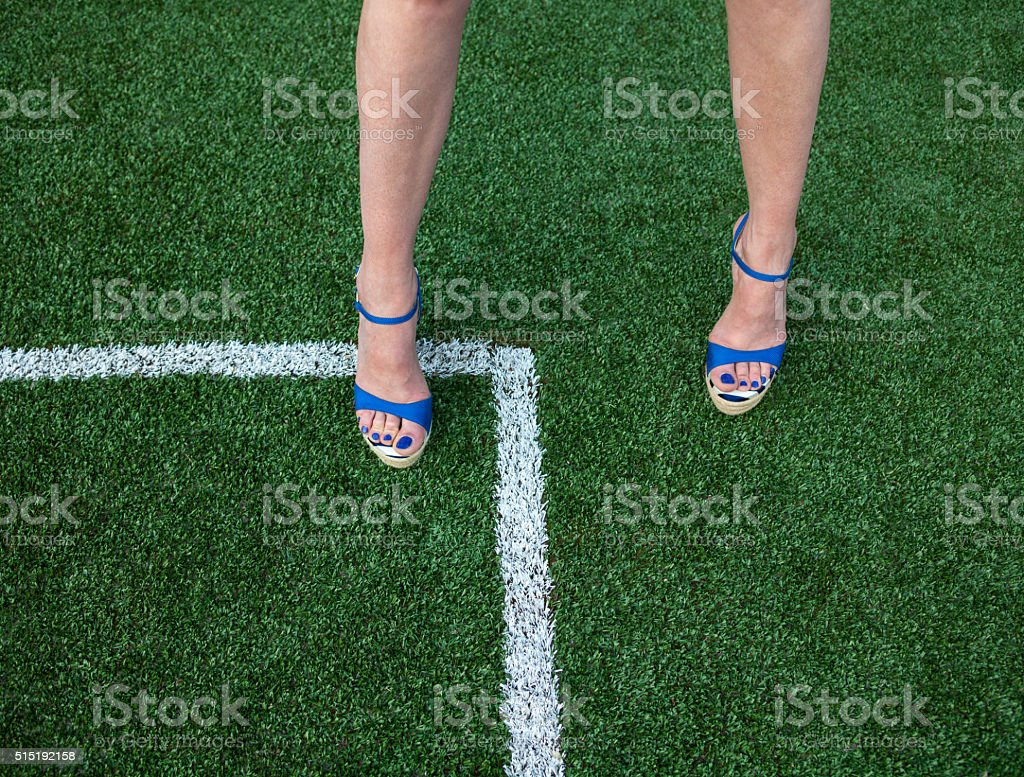 Woman legs on the soccer field stock photo