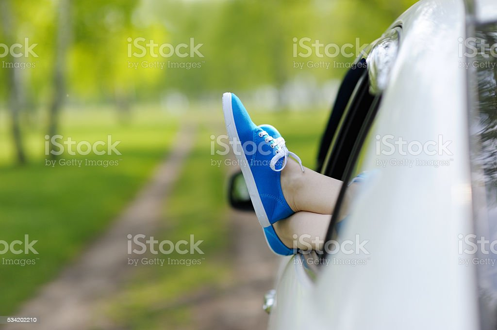 Woman legs out the Windows in the car. stock photo