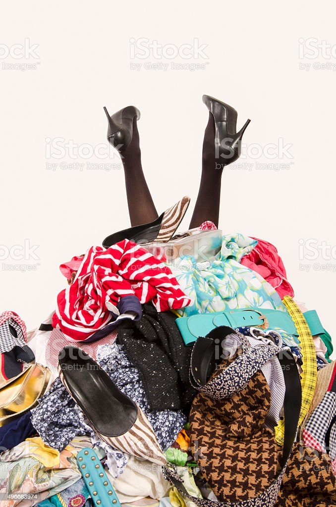 Woman legs reaching out from a big pile of clothes. stock photo