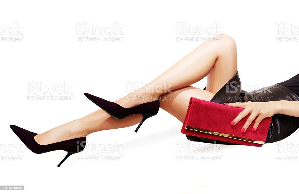Woman legs sexy black heels,red purse. Isolated on white. stock photo
