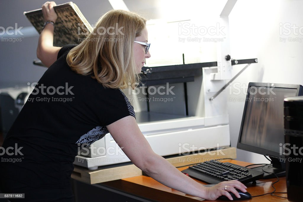Woman Librarian scanning large sheets of newspaper stock photo
